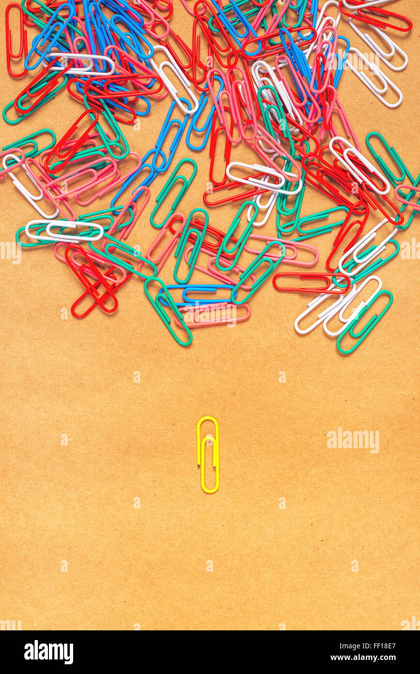 Flat lay colorful paper clips arrangement on kraft paper background, concept of racism and segregation. - Stock Image