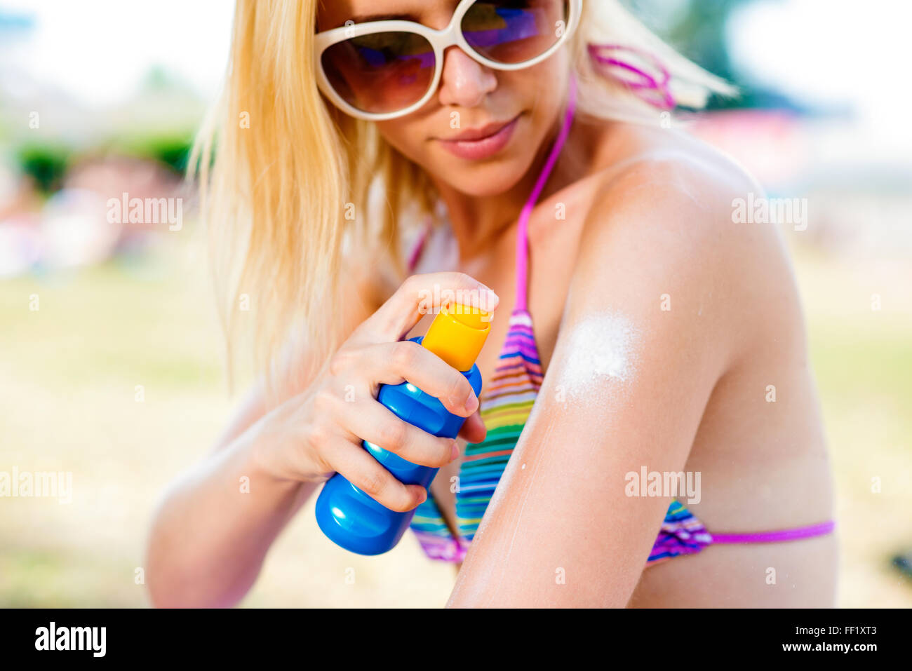 Blond woman in bikini and sunglasses putting on sunscreen - Stock Image