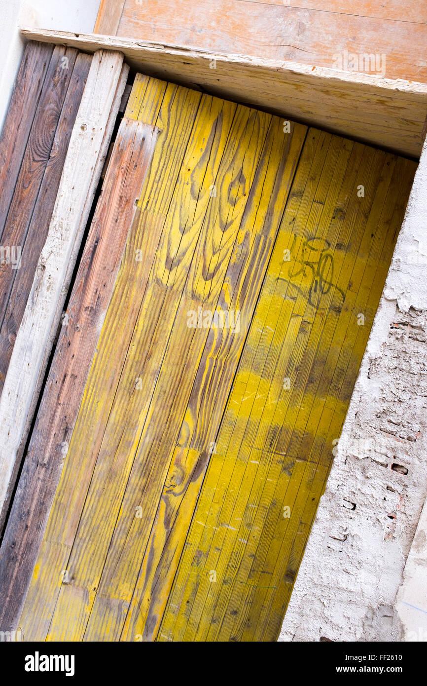 Yellow painted rustic wooden door partially open - Stock Image