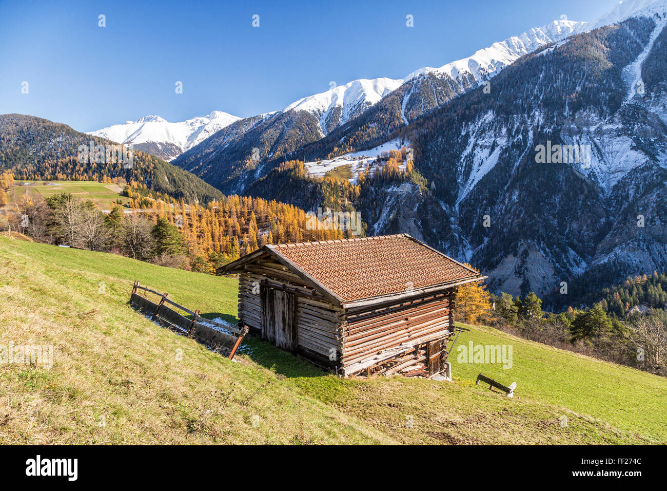 Wooden cabin surrounded by colorful woods and snowy peaks, Schmitten, Albula District, Canton of Graubunden, Switzerland, Stock Photo