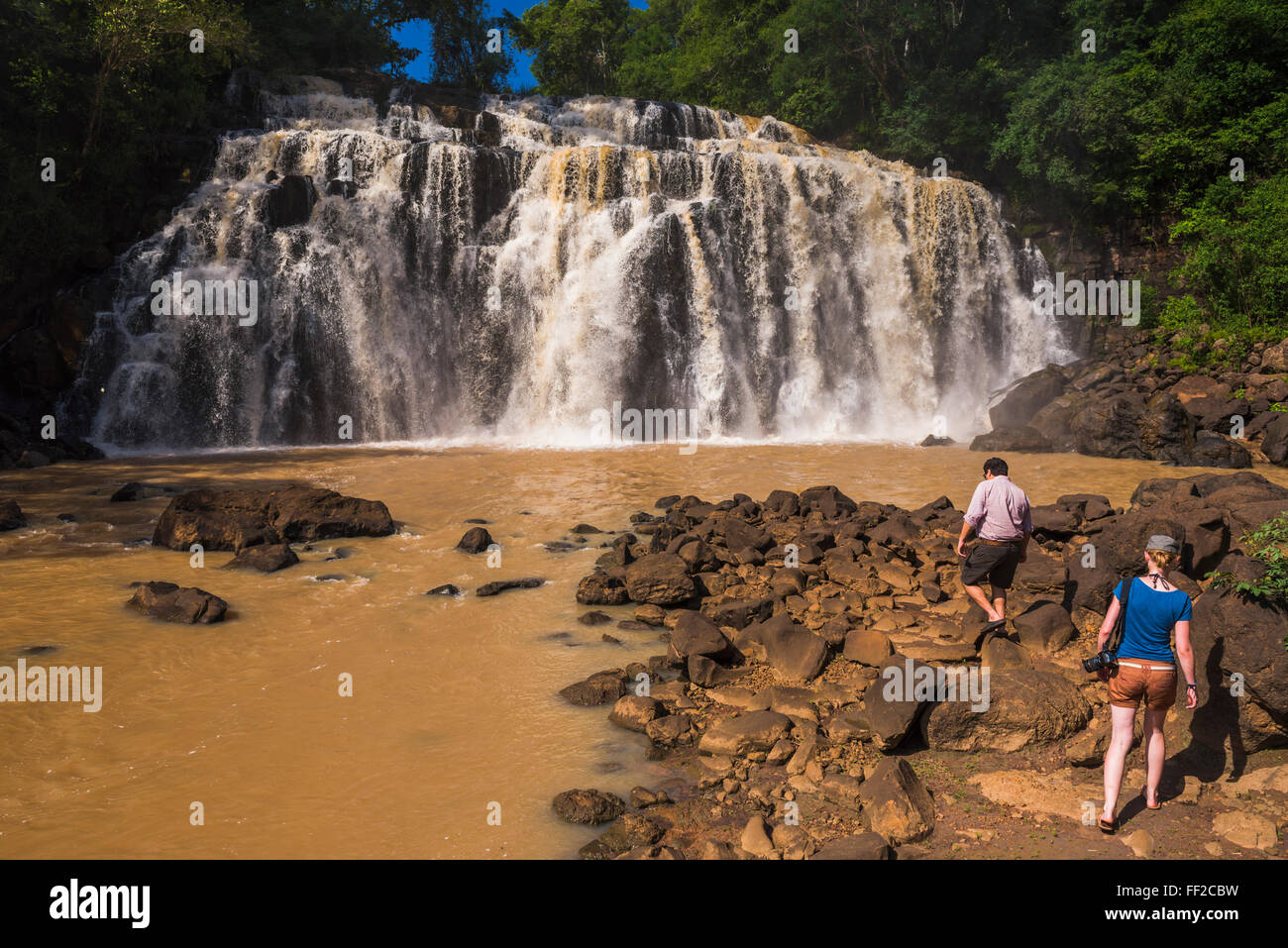 PeopRMe at waterfaRMRM connecting a tributary with the Rio Parana (Parana River), near Puerto Iguazu, Misiones Province, - Stock Image