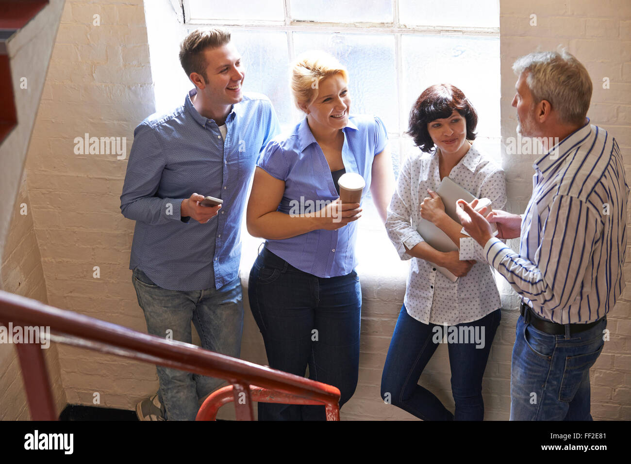 Businesspeople Having Informal Meeting On Office Stairs - Stock Image