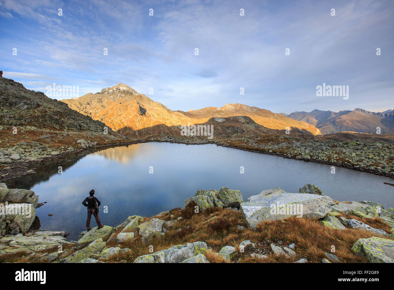 Hiker admires RMake Bergsee at sunrise, Chiavenna VaRMRMe, SpRMuga VaRMRMey, SwitzerRMand, Europe - Stock Image