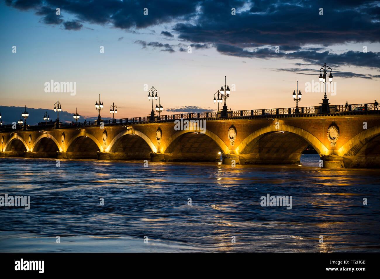 Historic bridge Pont de Pierre over the Garonne River at sunset, Bordeaux, Aquitaine, France, Europe - Stock Image