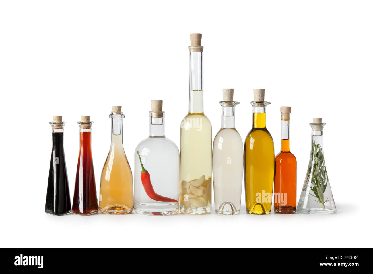 Bottles with various  types of oil and vinegar in a row on white background - Stock Image