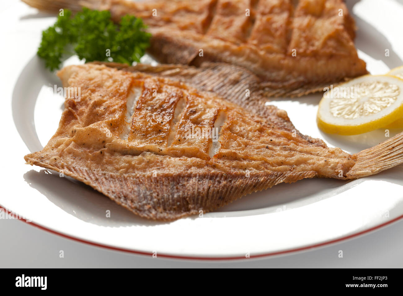 Dish with fried plaice, lemon and parsley - Stock Image