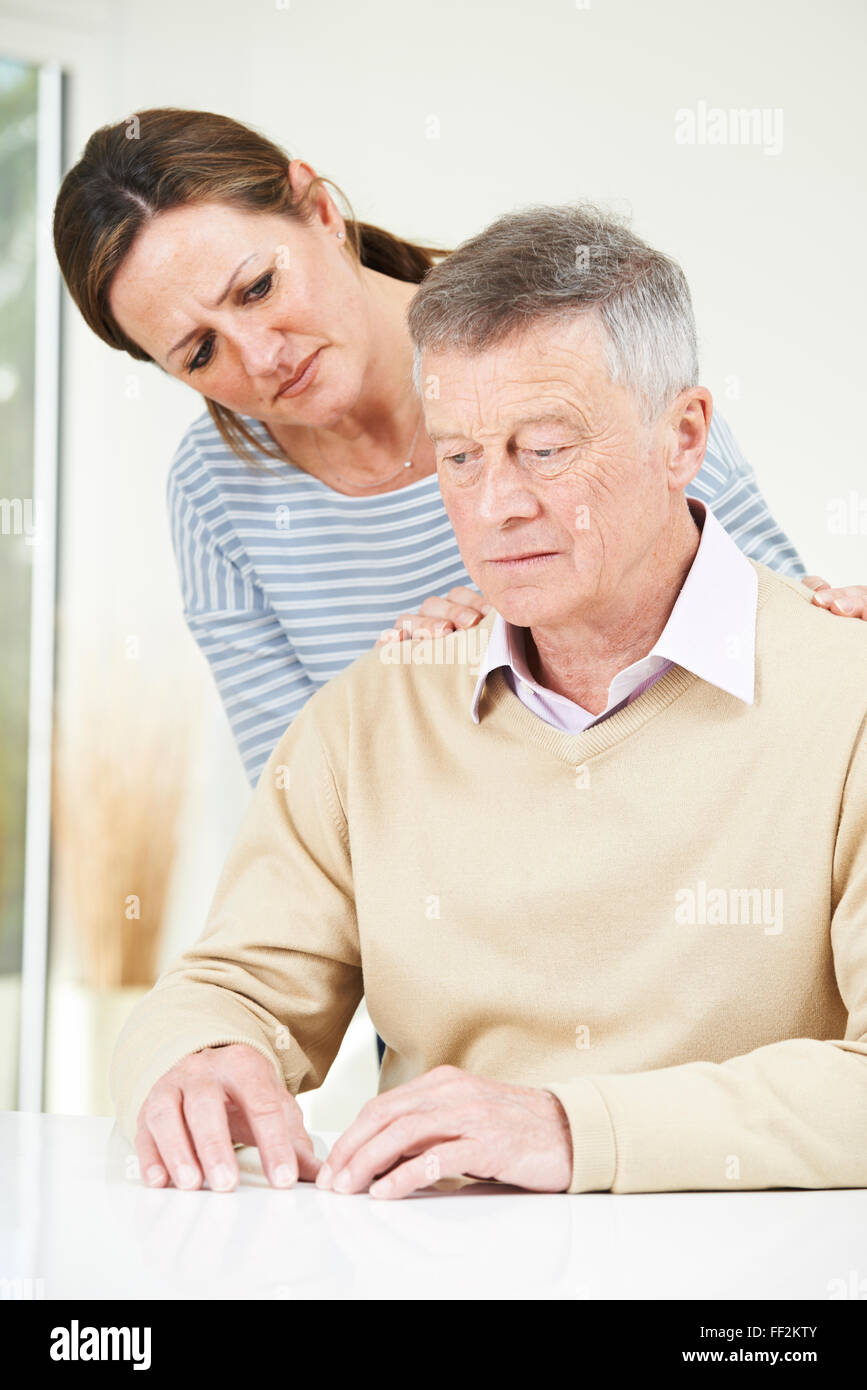 Confused Senior Man With Adult Daughter At Home - Stock Image