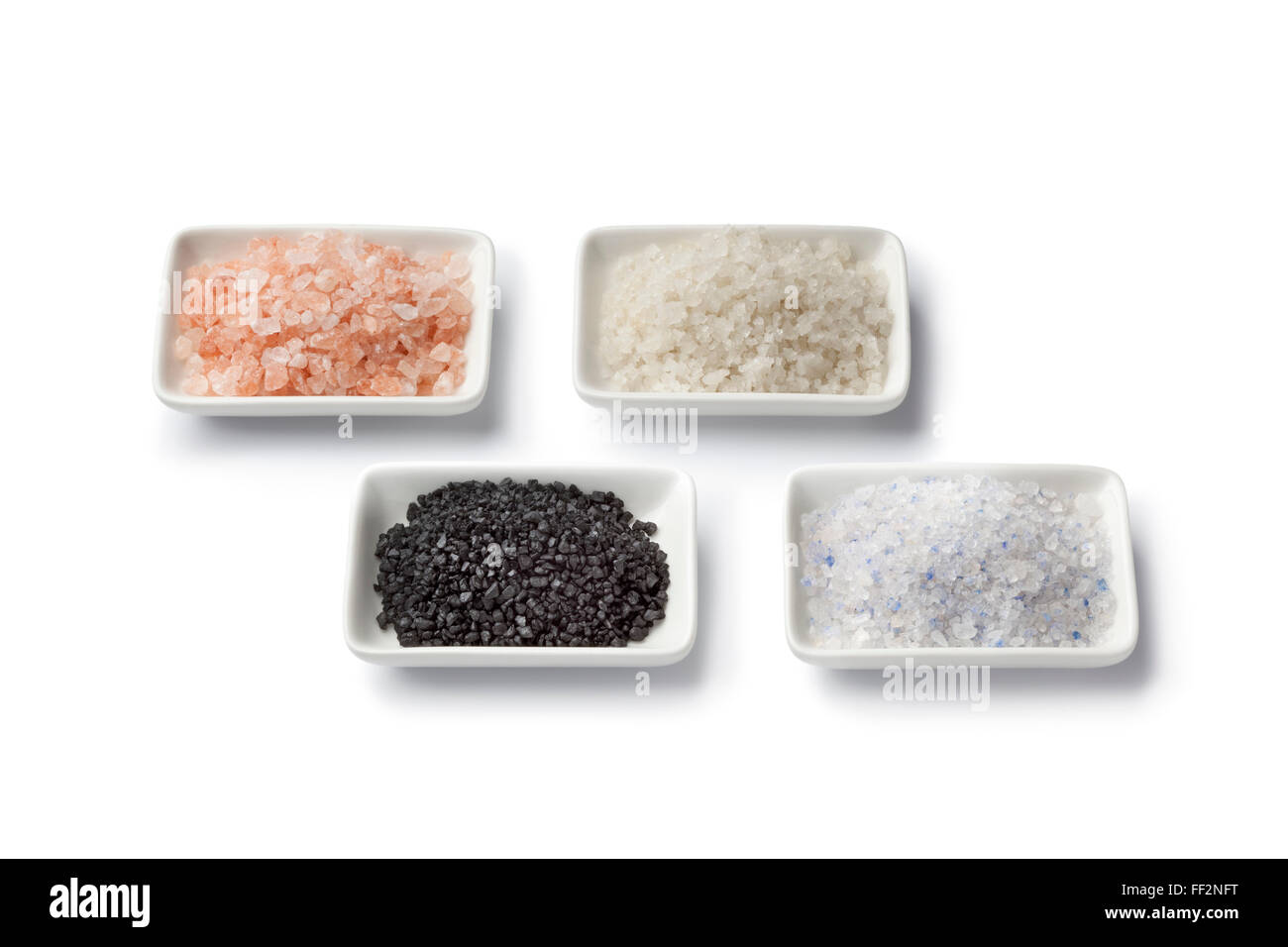 Four various types of salt in white dishes close up - Stock Image