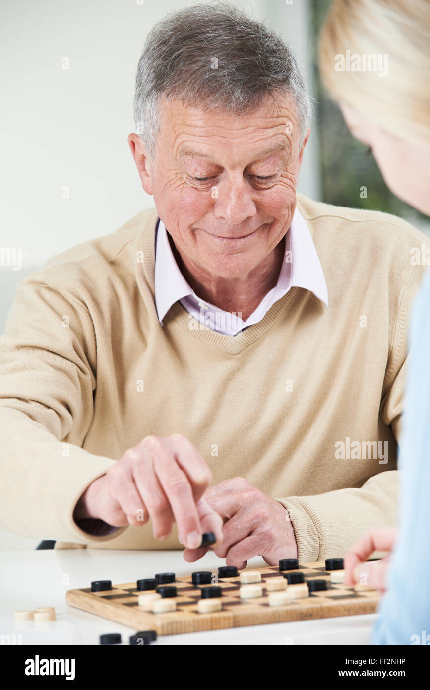 Senior Man Playing Checkers With Teenage Daughter Stock Photo