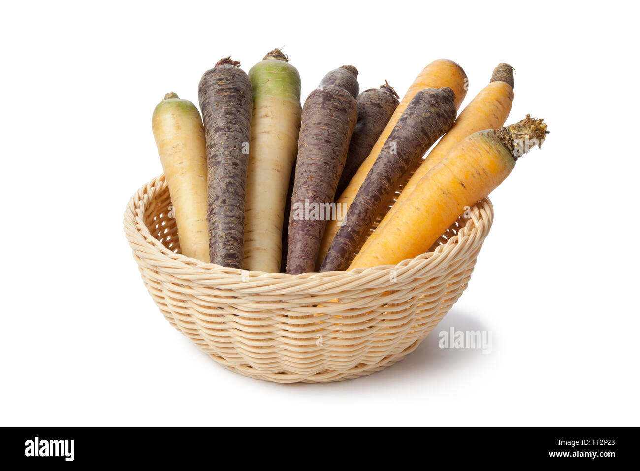 Fresh raw black, white and yellow carrots in a basket on white background - Stock Image