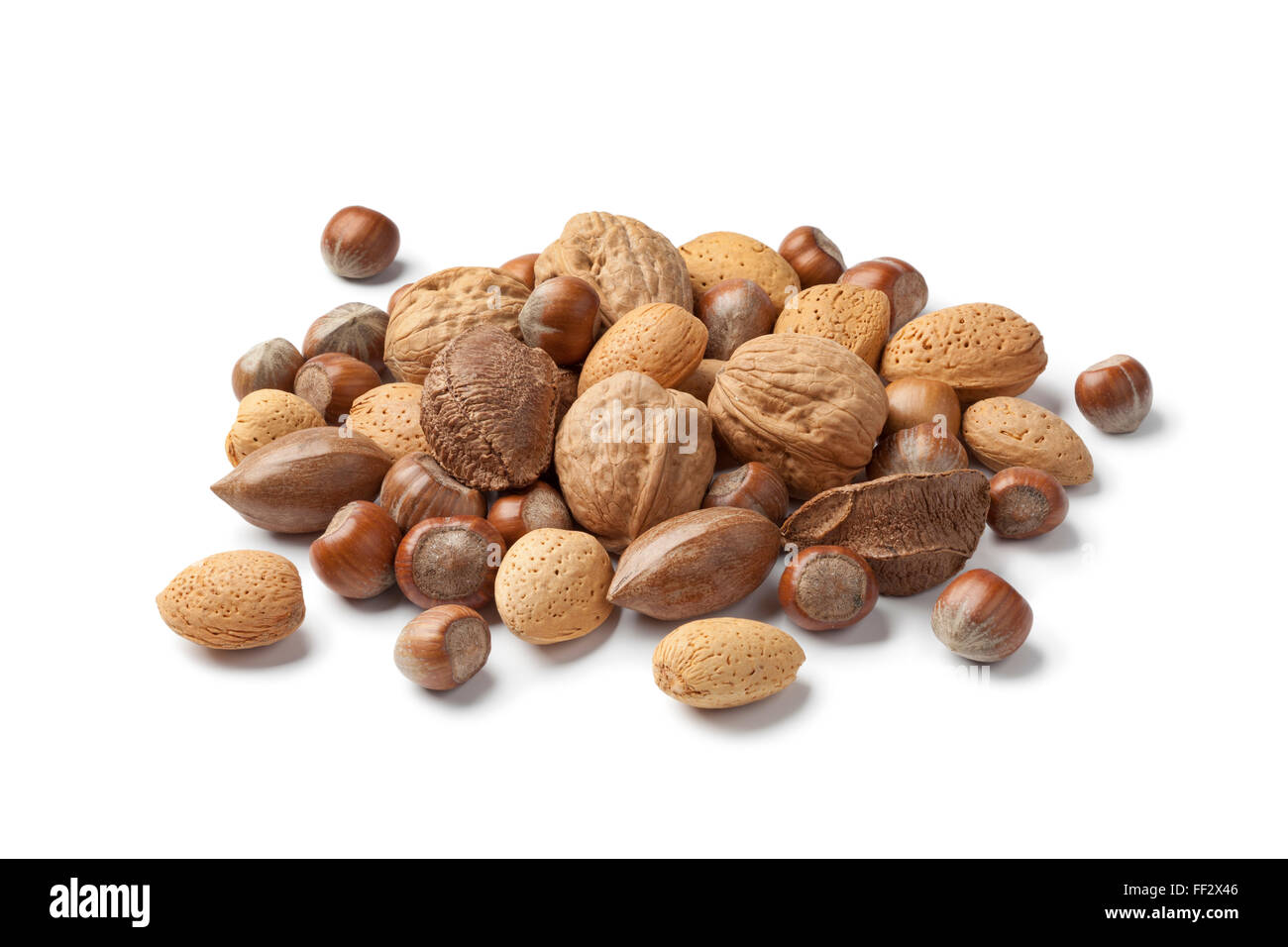 Heap of mixed nuts in the shell on white background - Stock Image