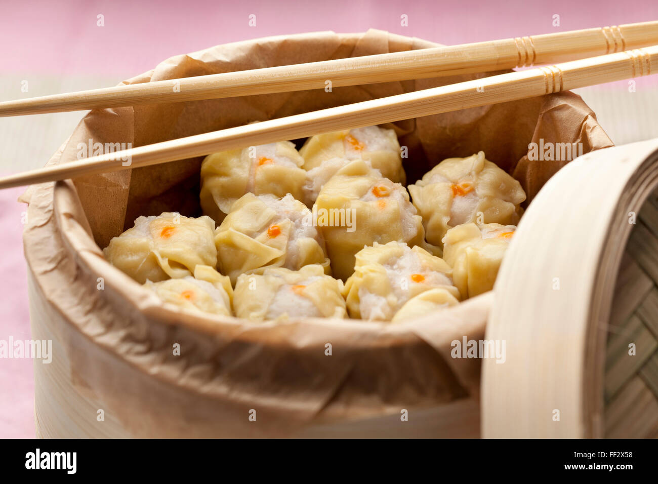 Chinese Dim Sum in a steaming basket with chopsticks - Stock Image