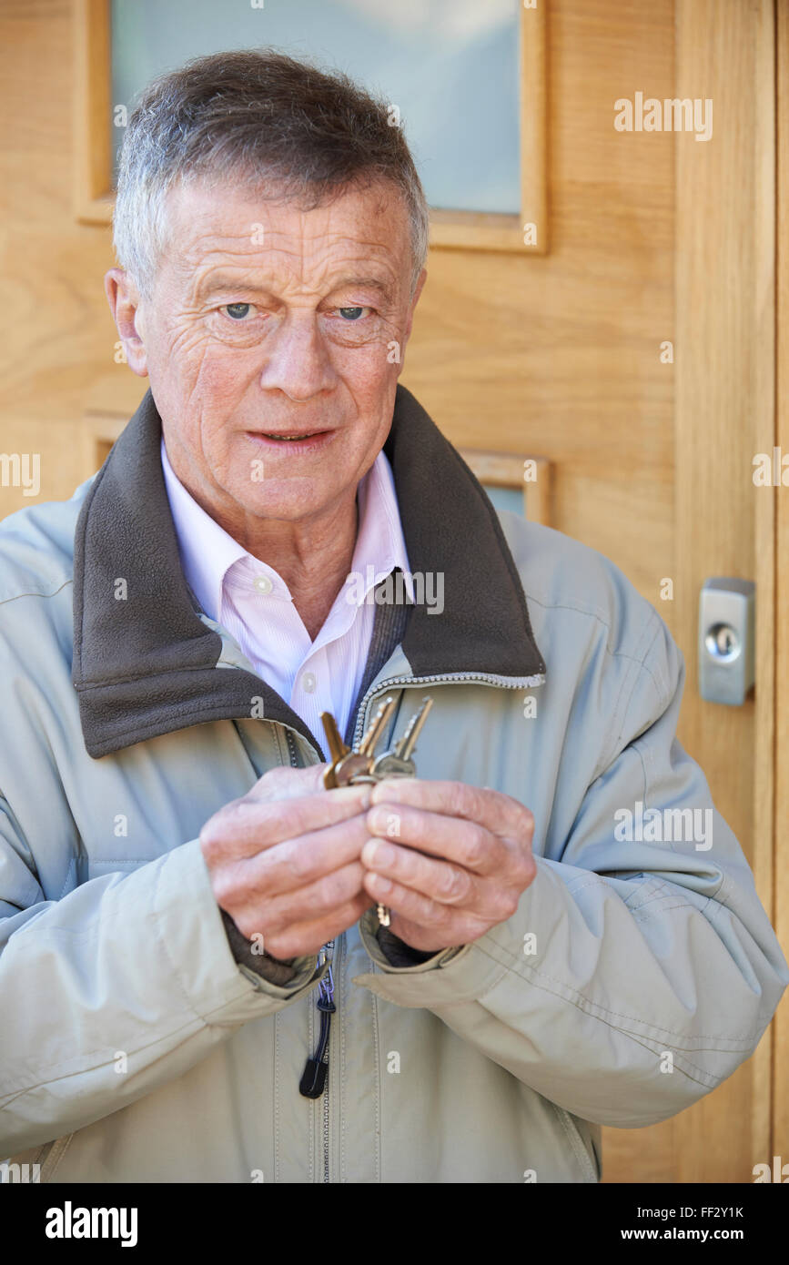 Confused Senior Man Trying To Find Door Key - Stock Image
