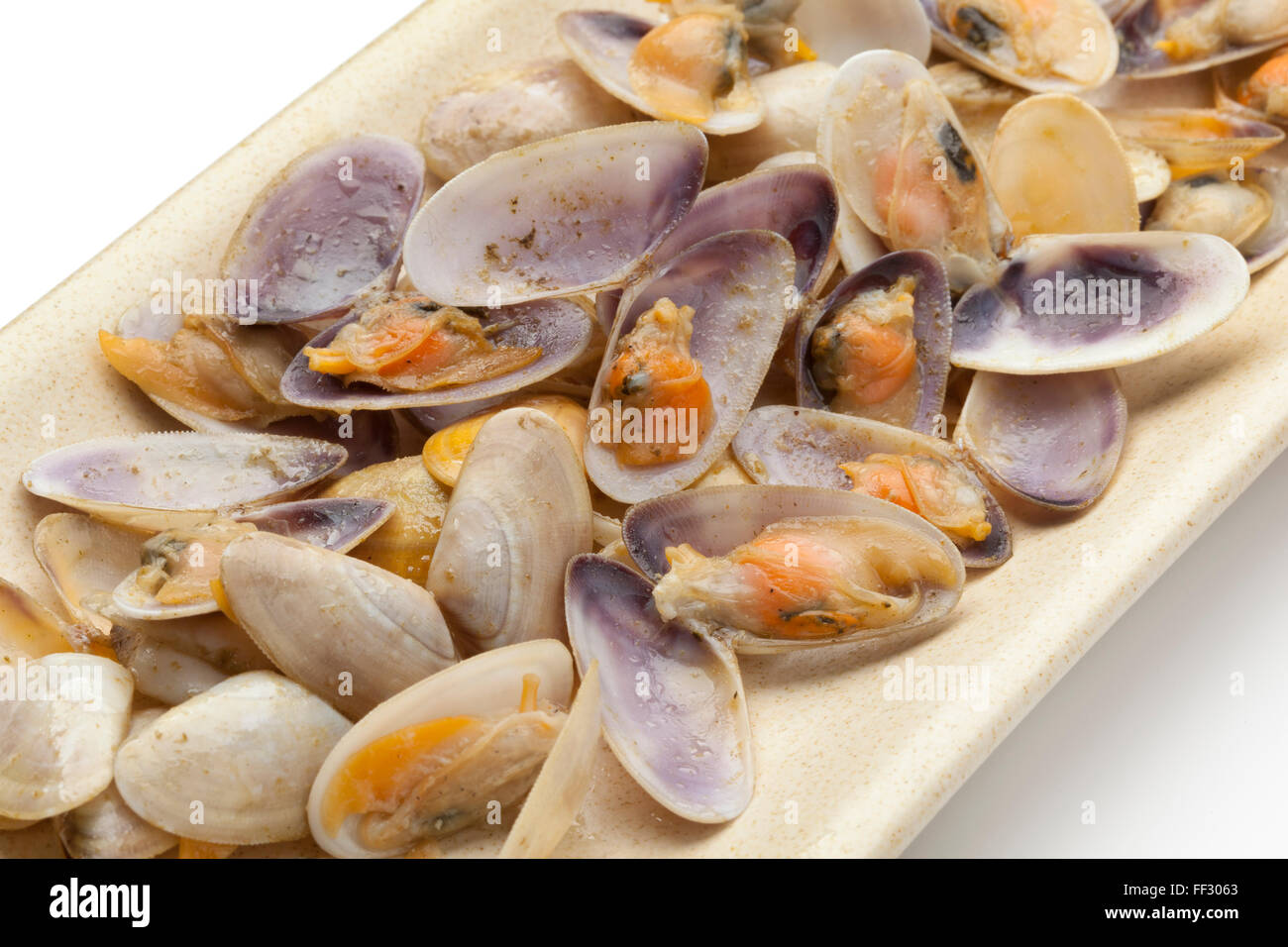 Cooked banded wedge shells on a dish on white background - Stock Image