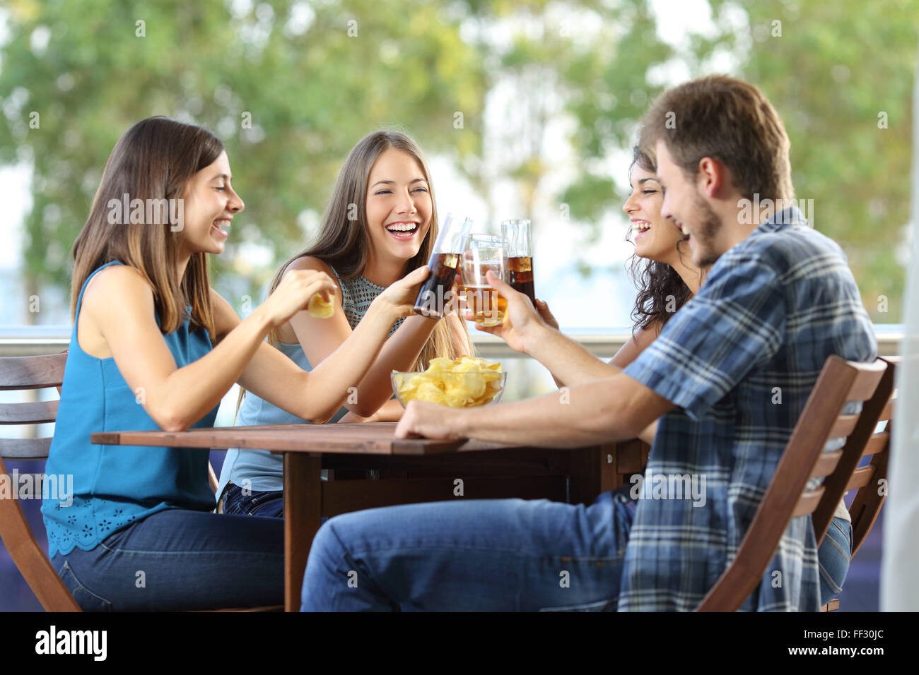 Group of 4 happy friends toasting in an hotel or home terrace Stock Photo