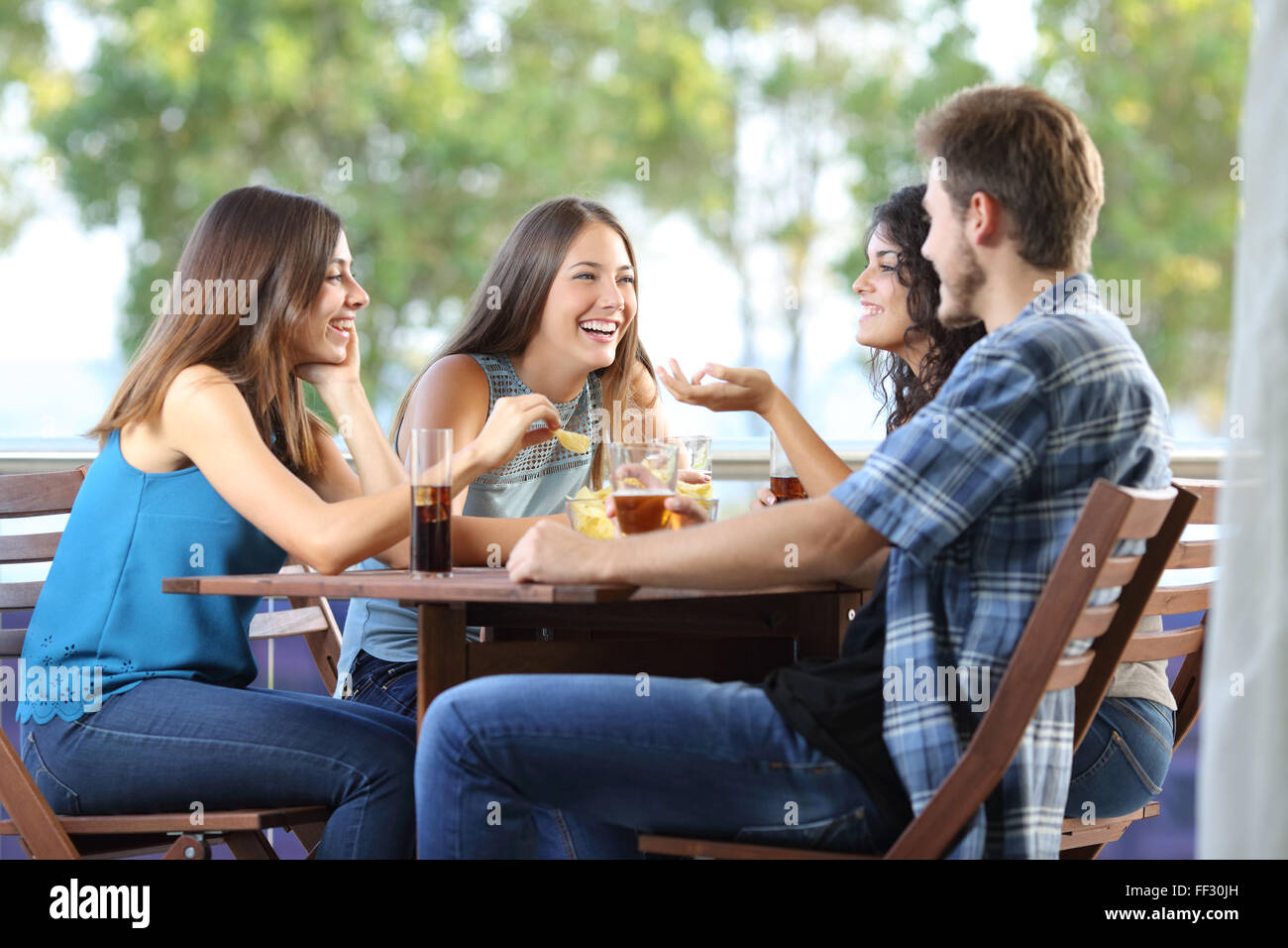 Group of four friends talking and drinking sitting in a terrace at home - Stock Image