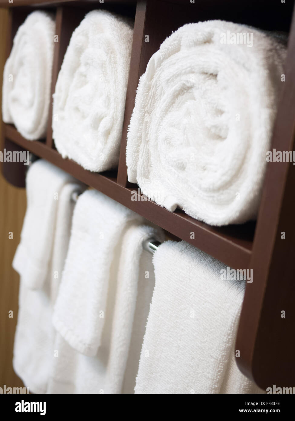 Bathroom Towel Rack With Rolled And Hanging Towels In A Hotel Bathroom