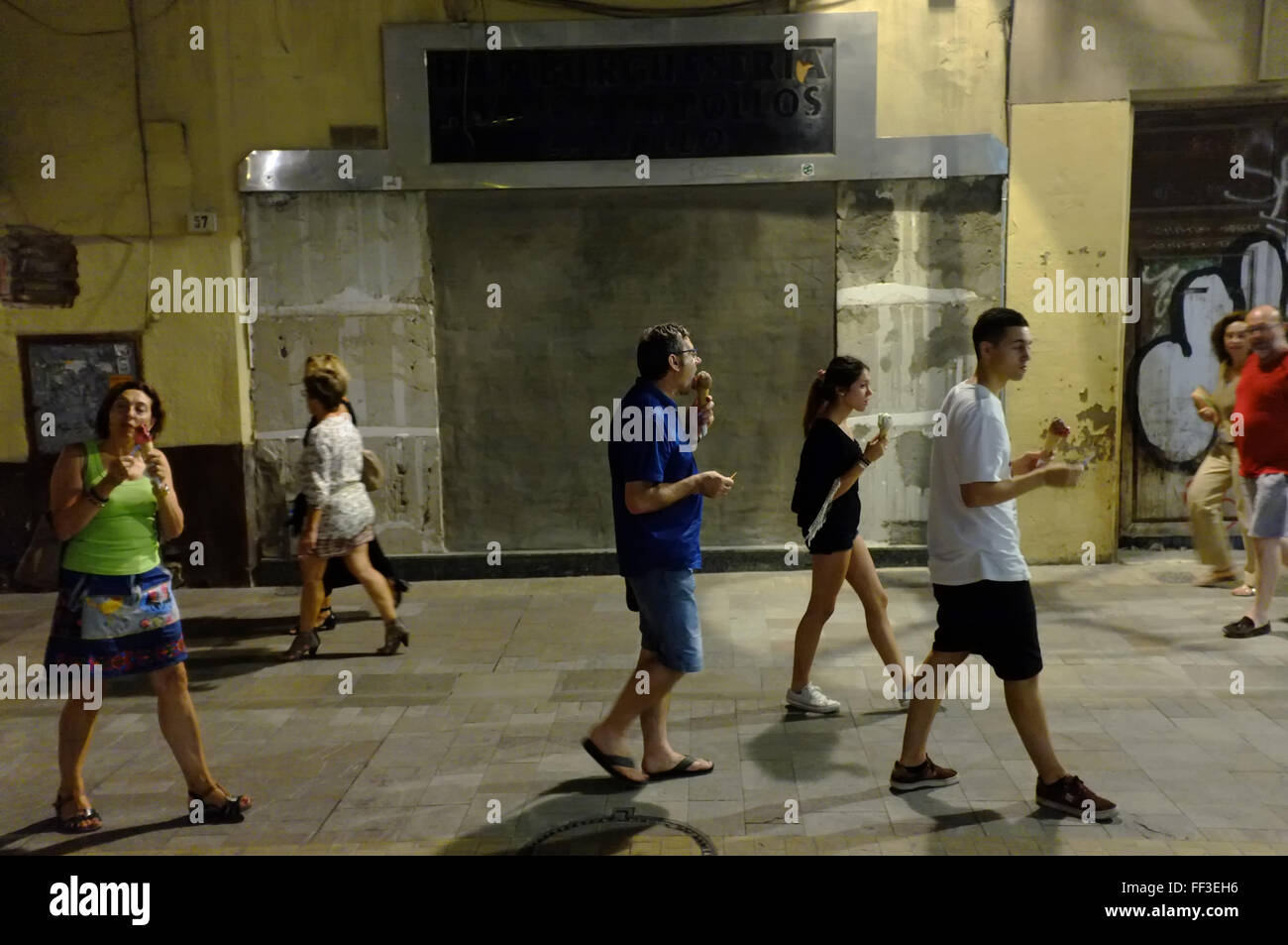 Spanish holidaymakers in Malaga, Spain eating ice creams in the evening - Stock Image