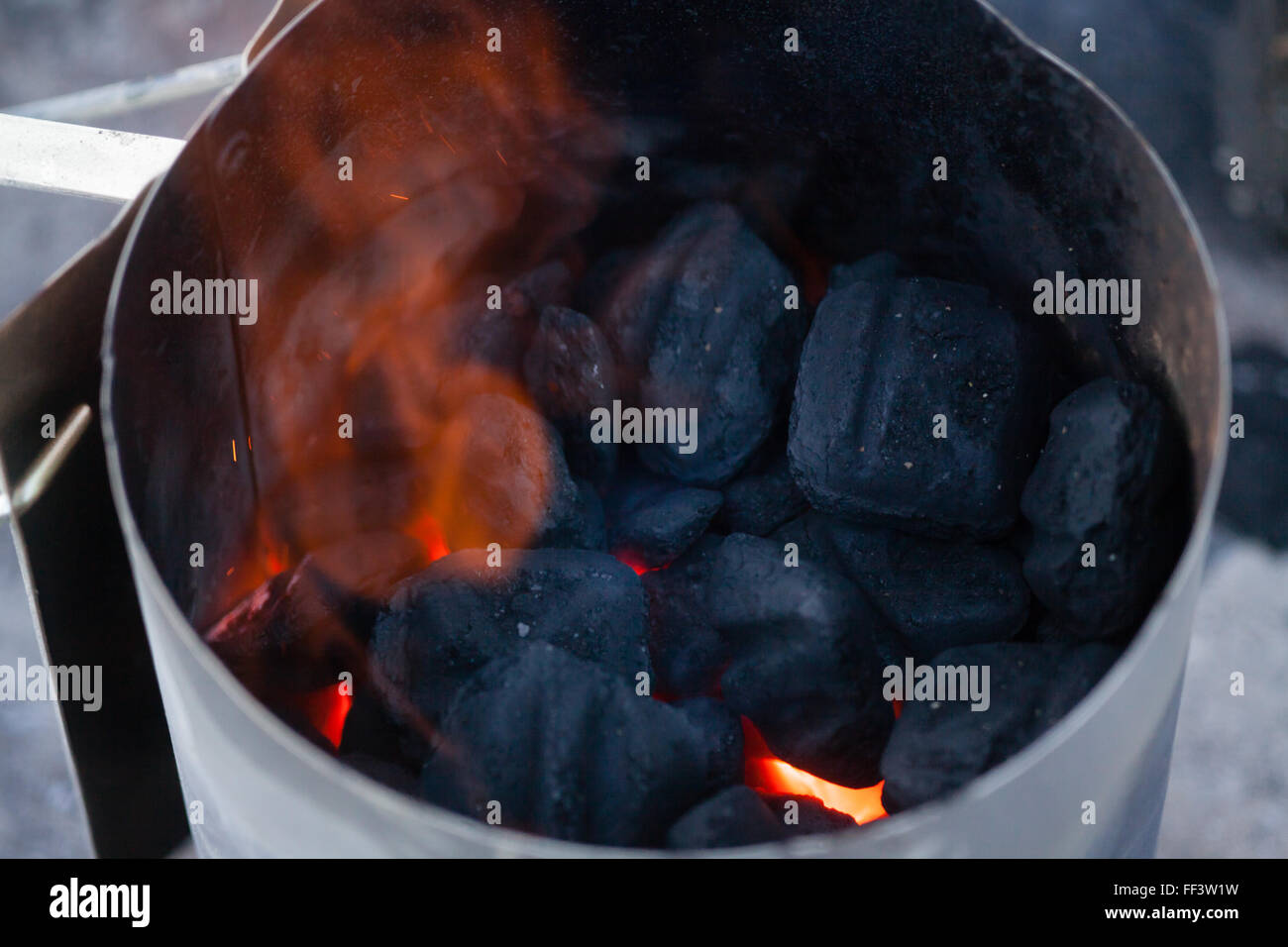 Charcoal burning in metal container - Stock Image