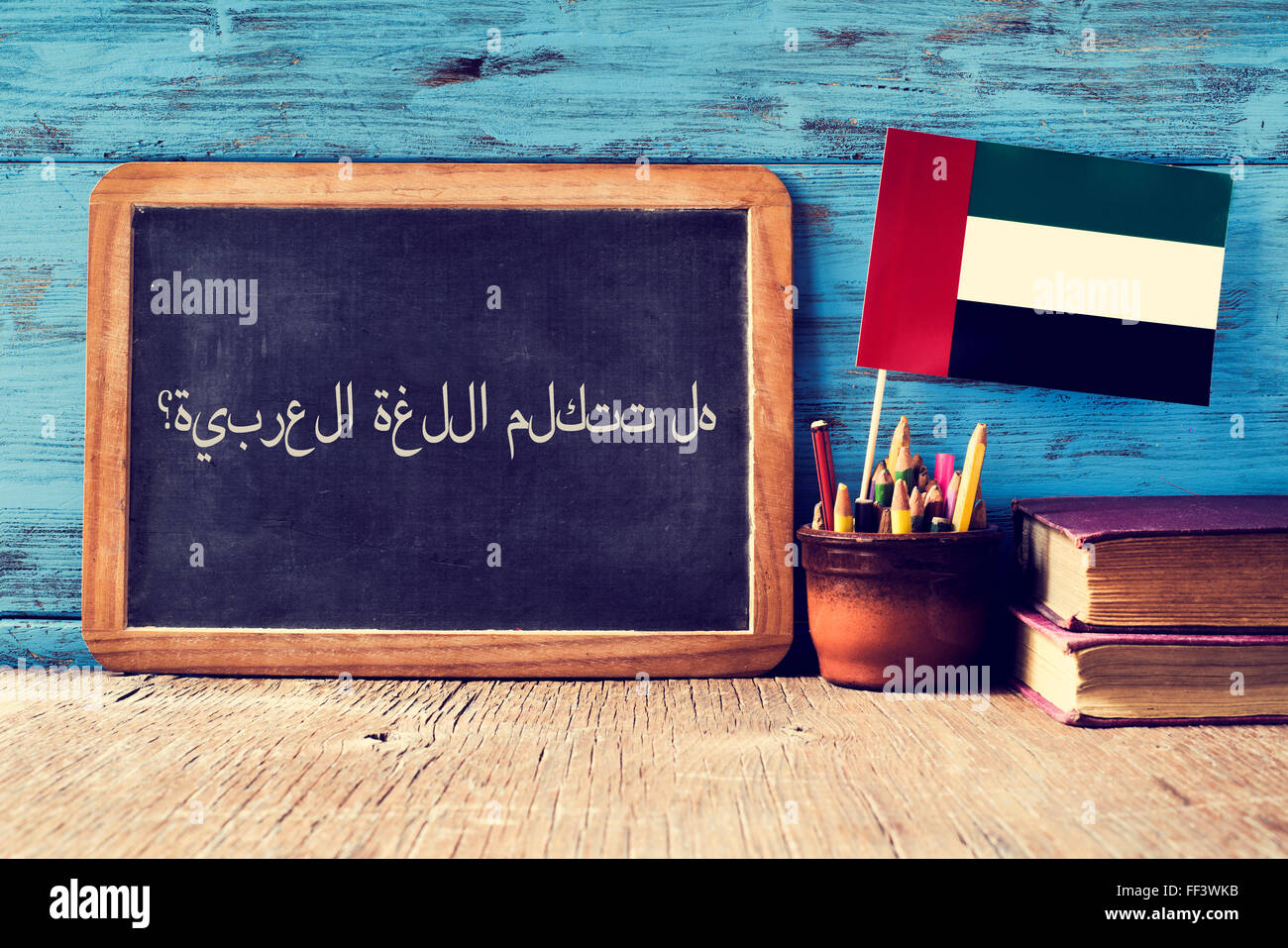 a chalkboard with the question do you speak Arabic? written in Arabic, a pot with pencils, some books and the flag - Stock Image