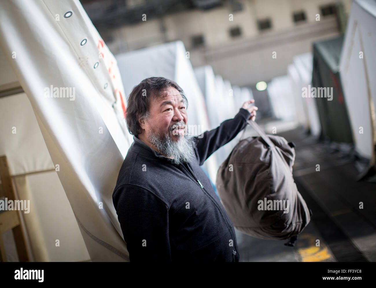 Berlin, Germany. 10th Feb, 2016. Chinese artist Ai Weiwei talks to his film crew in the refugee emergency shelter - Stock Image