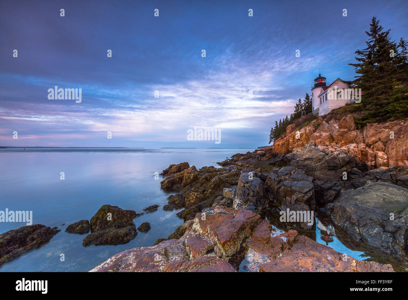 The iconic Bass Harbor Head Lighthouse is reflected in a tidepool at sunrise in Acadia National Park, Mount Desert Stock Photo