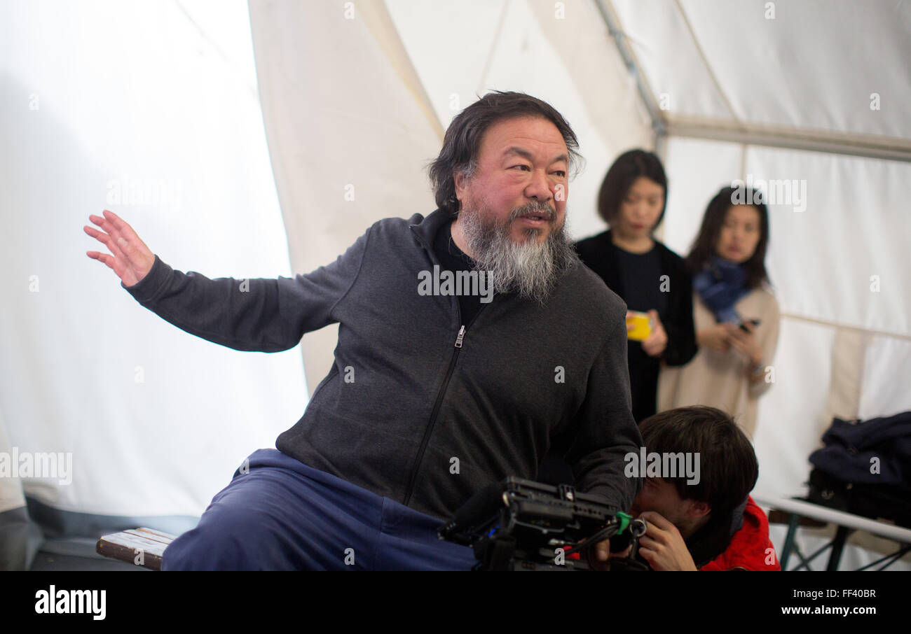 Berlin, Germany. 10th Feb, 2016. Chinese artist Ai Weiwei (L) talks to his film crew in the refugee emergency shelter - Stock Image