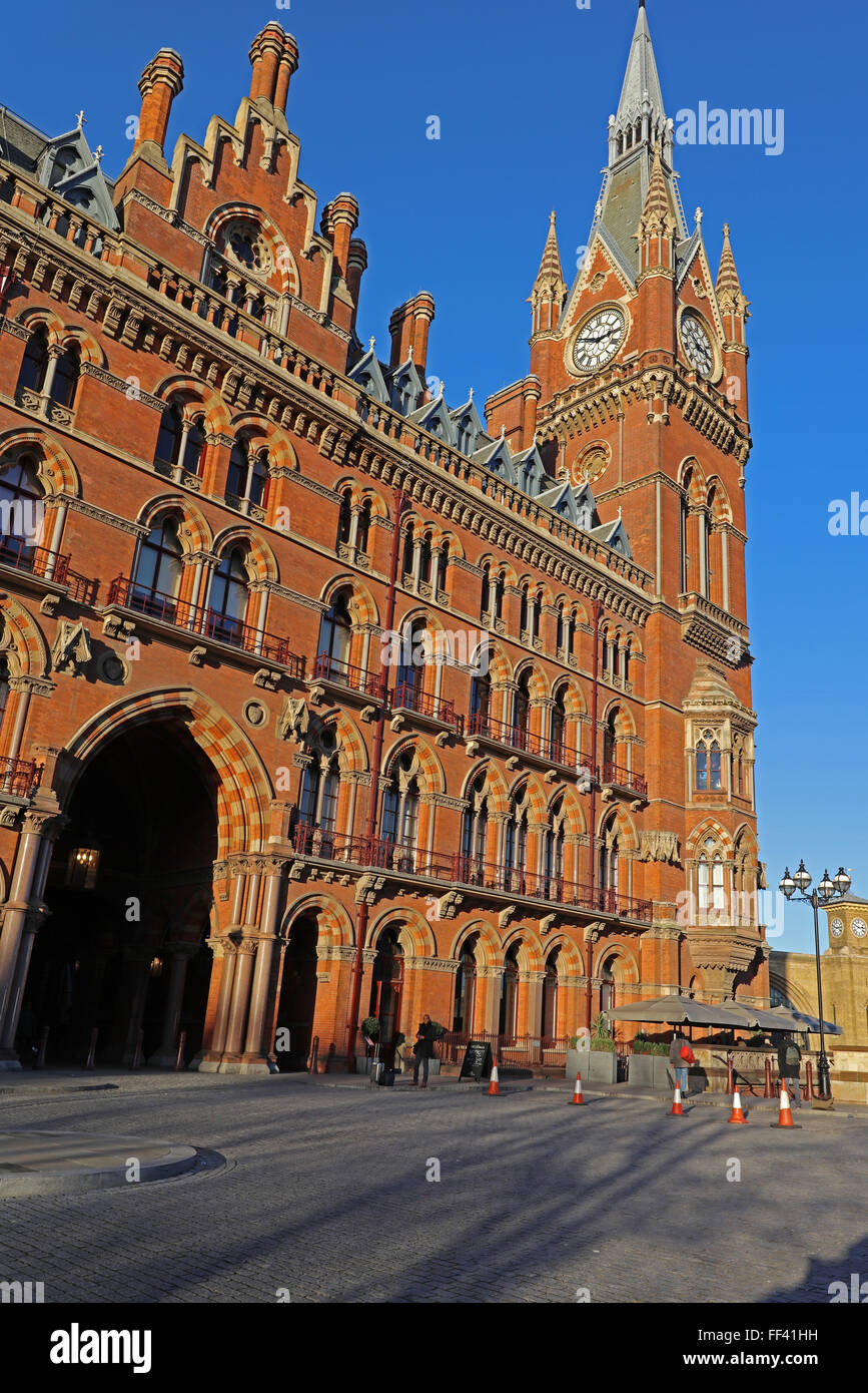 A side view of Saint Pancras Railway station with its huge clock tower and multiple windows facing the road - Stock Image