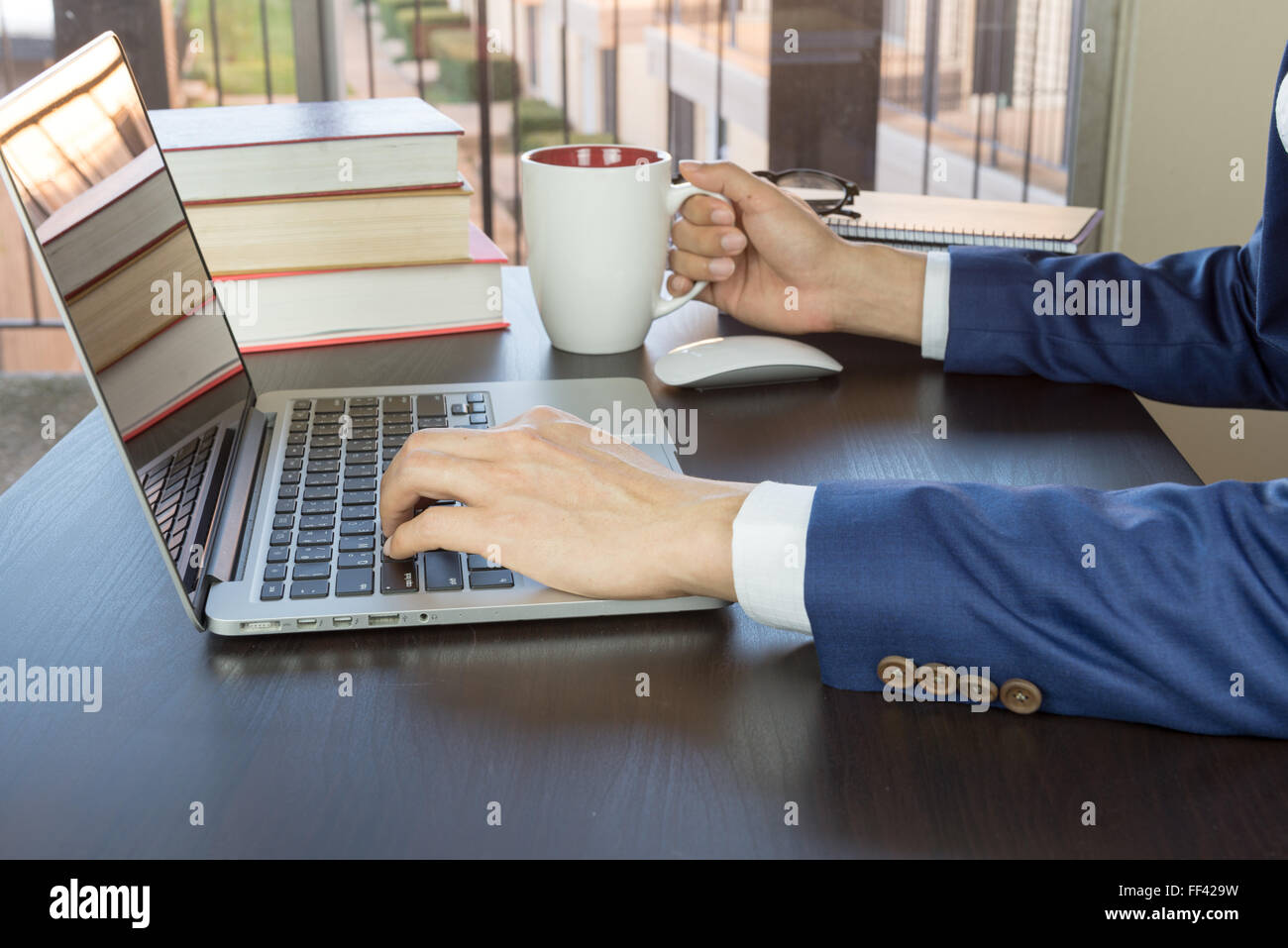 man in suit working in office desk, grabing cup of coffee Stock Photo