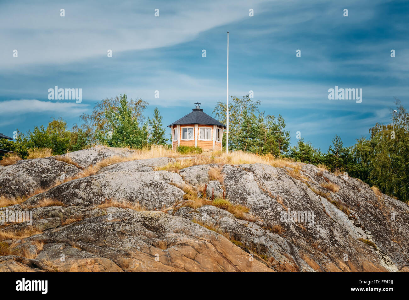 Yellow Finnish Lookout Wooden House On Rock In Island In Summer - Stock Image