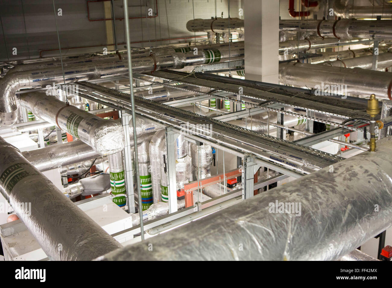 Foil insulated heating system pipes, inside the boiler room of a ...