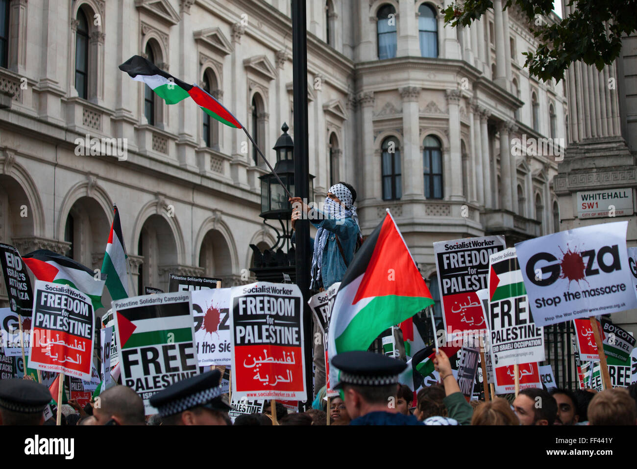 A protester raises the Palestinian flag at a free Gaza demonstration in London - Stock Image