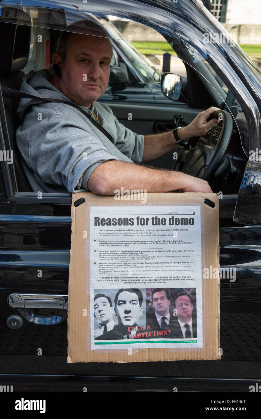London, UK. 10th February 2016. A black cab taxi driver with a notice explaining the reasons for the go-slow protest Stock Photo