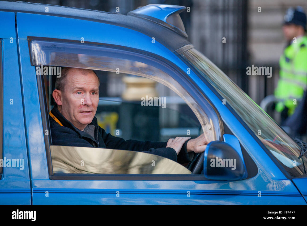 London, UK. 10th February 2016. A 'black cab' taxi driver during a go-slow protest in Whitehall against lack of Stock Photo