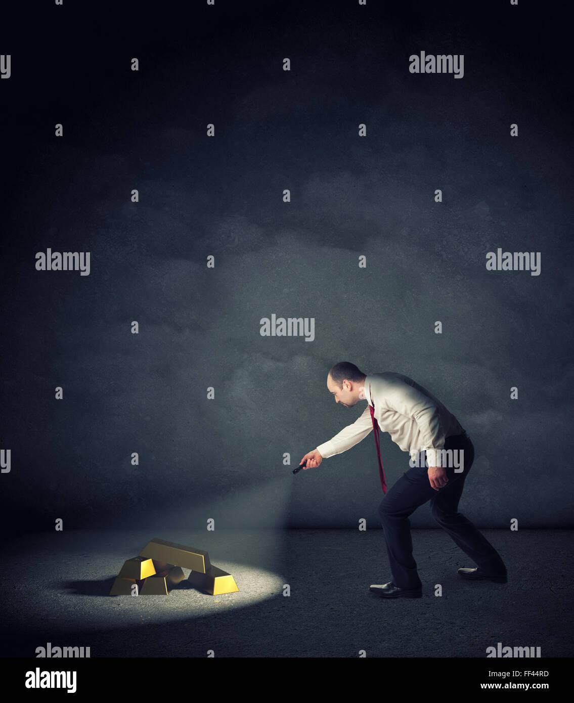 businessman with flashlight find gold ingot - Stock Image