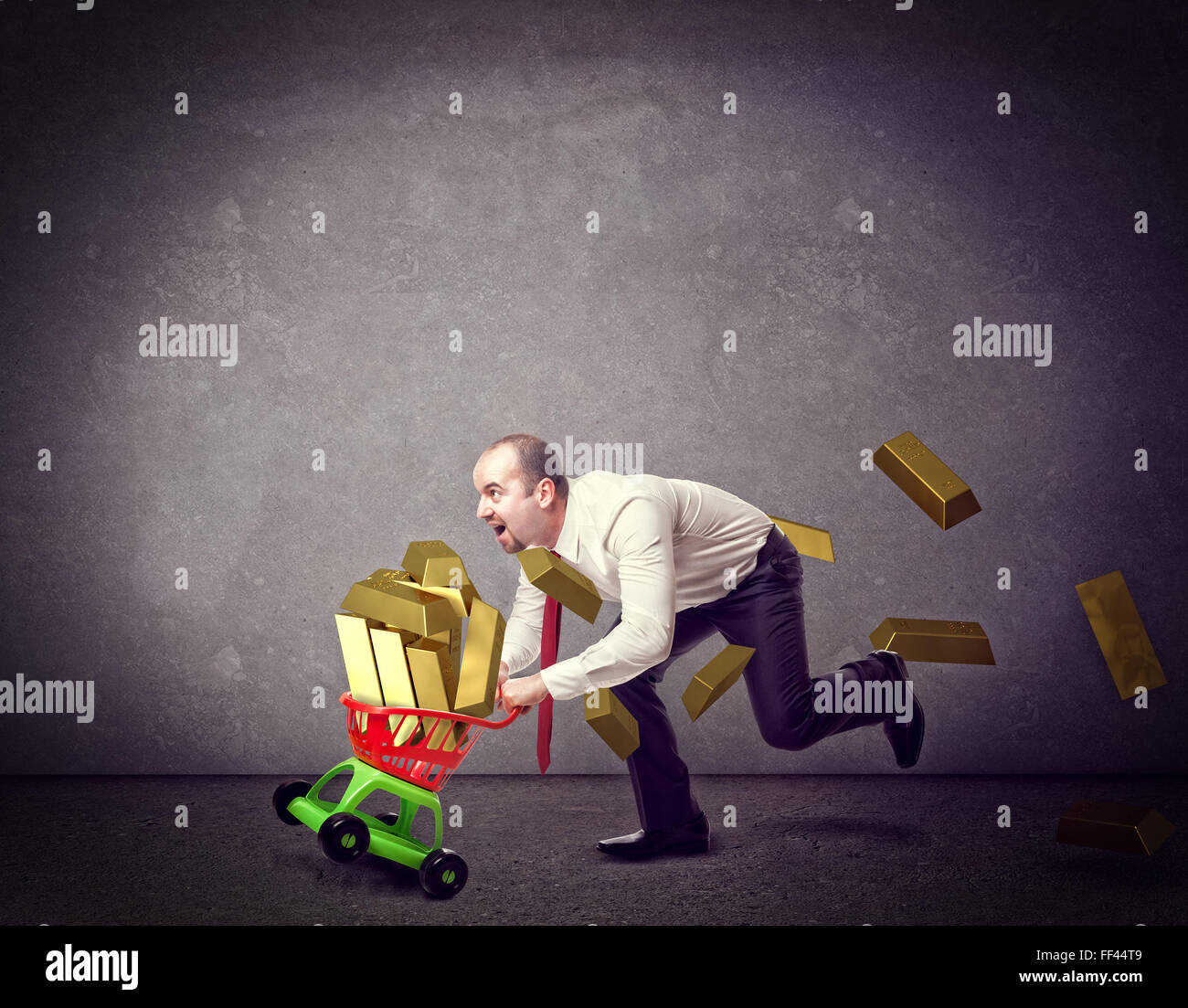 man with shopping troller toy and golden ingot - Stock Image