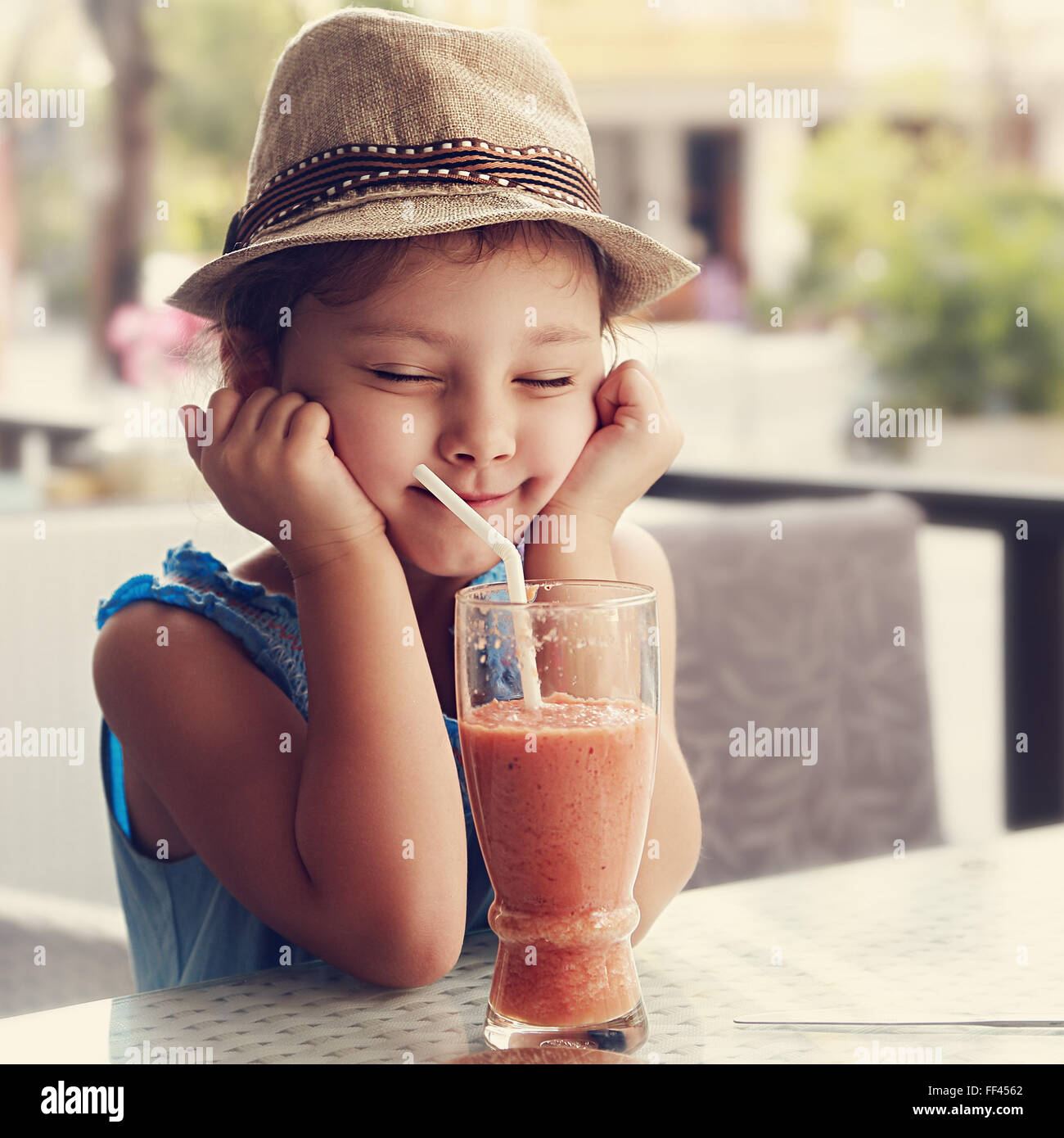 Fun kid girl in hat screwing up her eyes and waiting the moment to drink the smoothie tasty juice on summer background - Stock Image