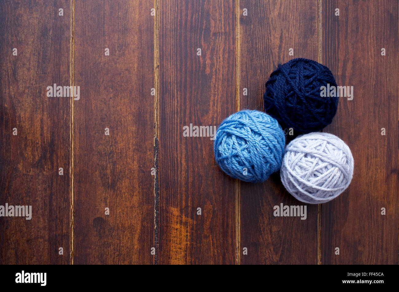 Three skeins in blue tones over wooden brown striped table - Stock Image