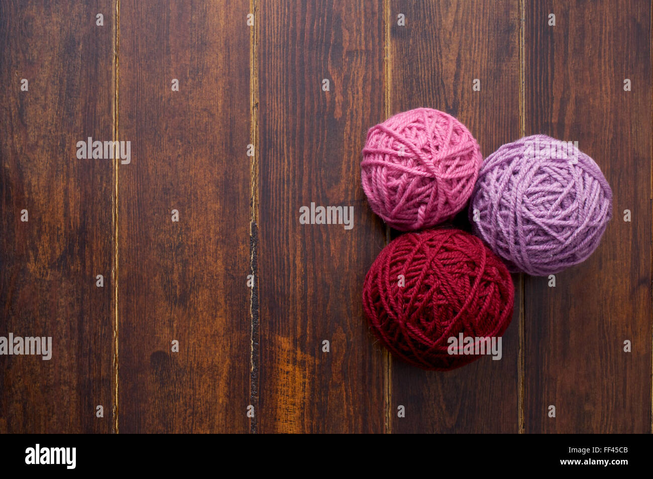 Three skeins in red and pink tones over wooden brown striped table Stock Photo
