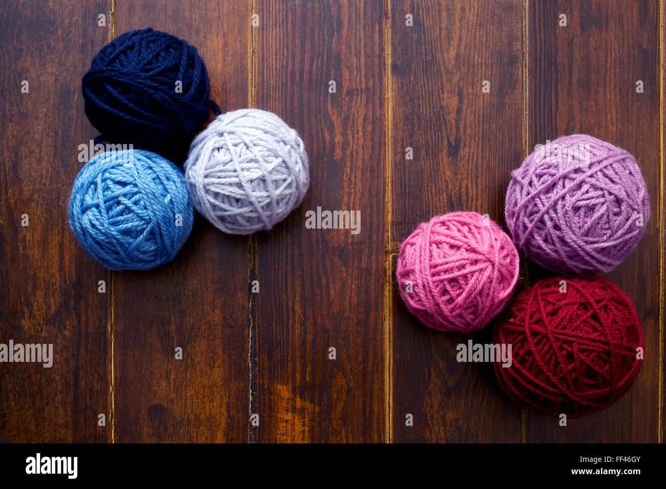 Six skeins in red and blue tones over wooden brown striped table - Stock Image