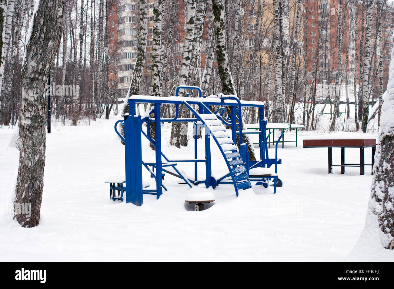 Blue exercise equipment with a lot of snow - Stock Image