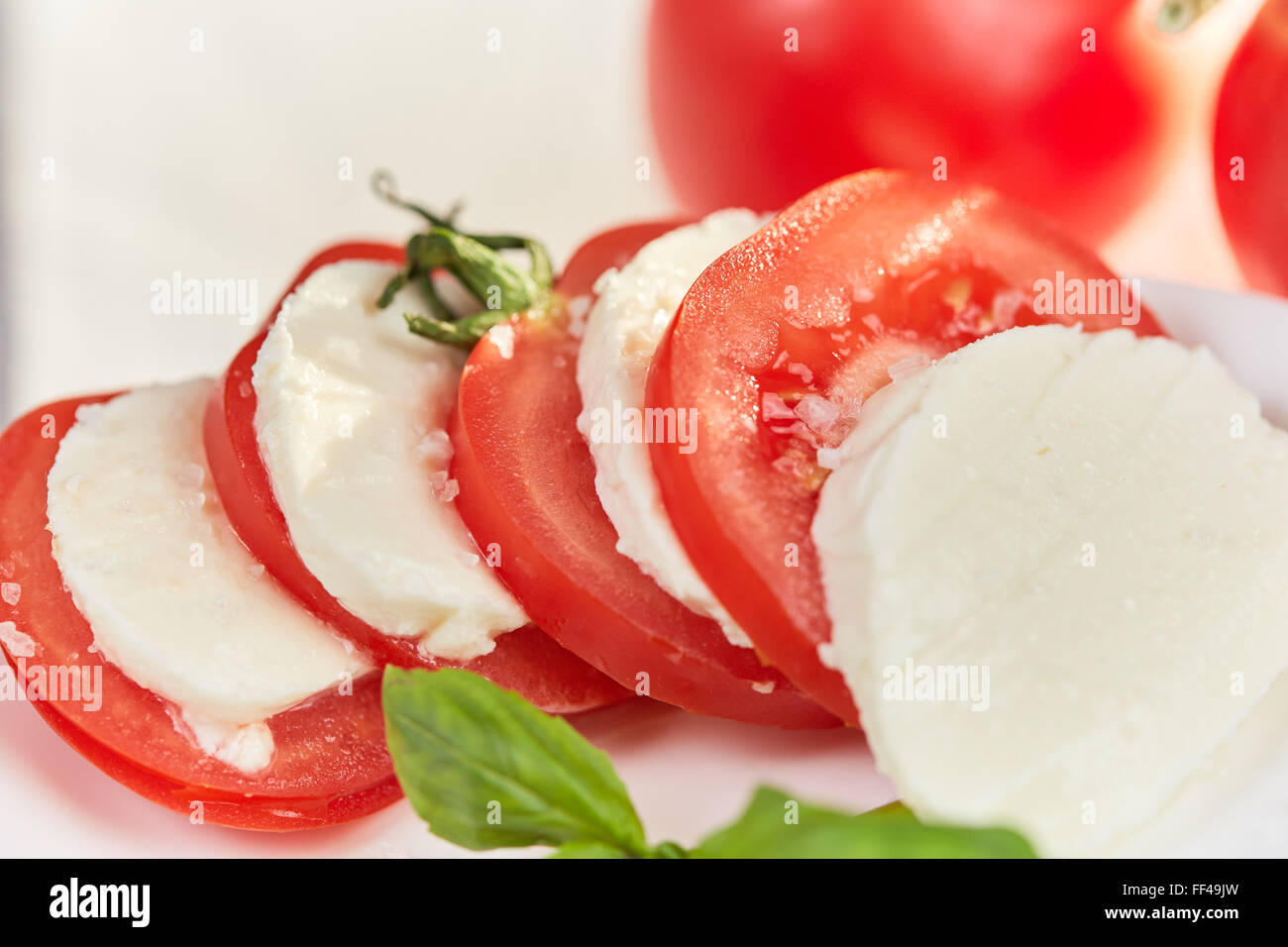 Macro highkey shot of tomatos with mozzarella and basil and big salt grains on a white table. - Stock Image
