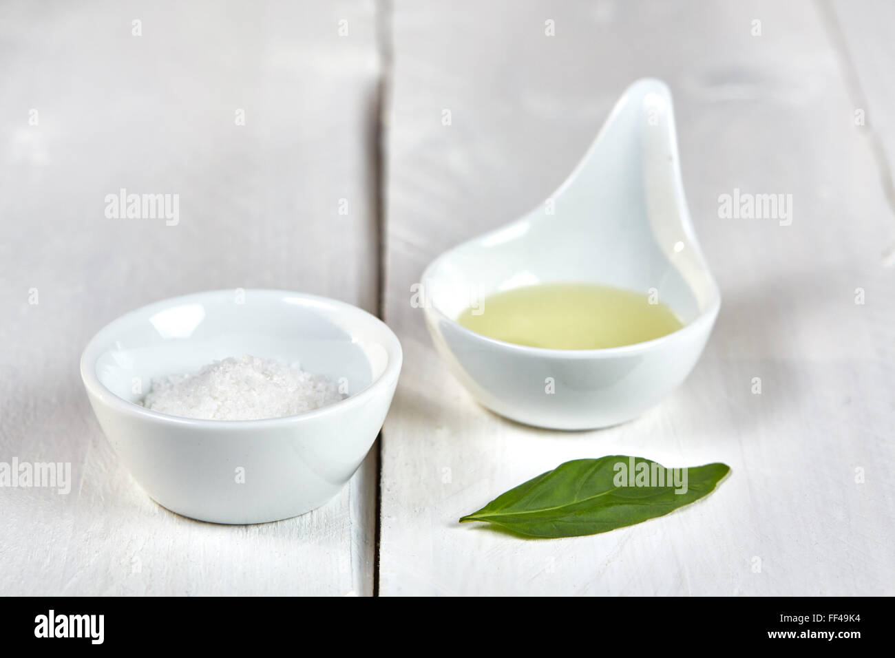 Salt and oil in dishes with a green basil leaf on a white wooden table. - Stock Image