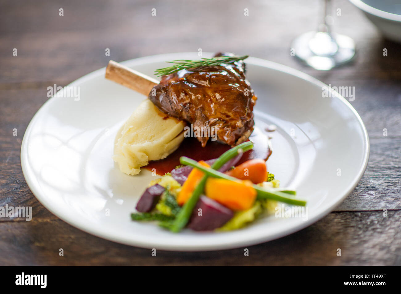 A lamb shank with mashed potato and vegetables on a plate - Stock Image