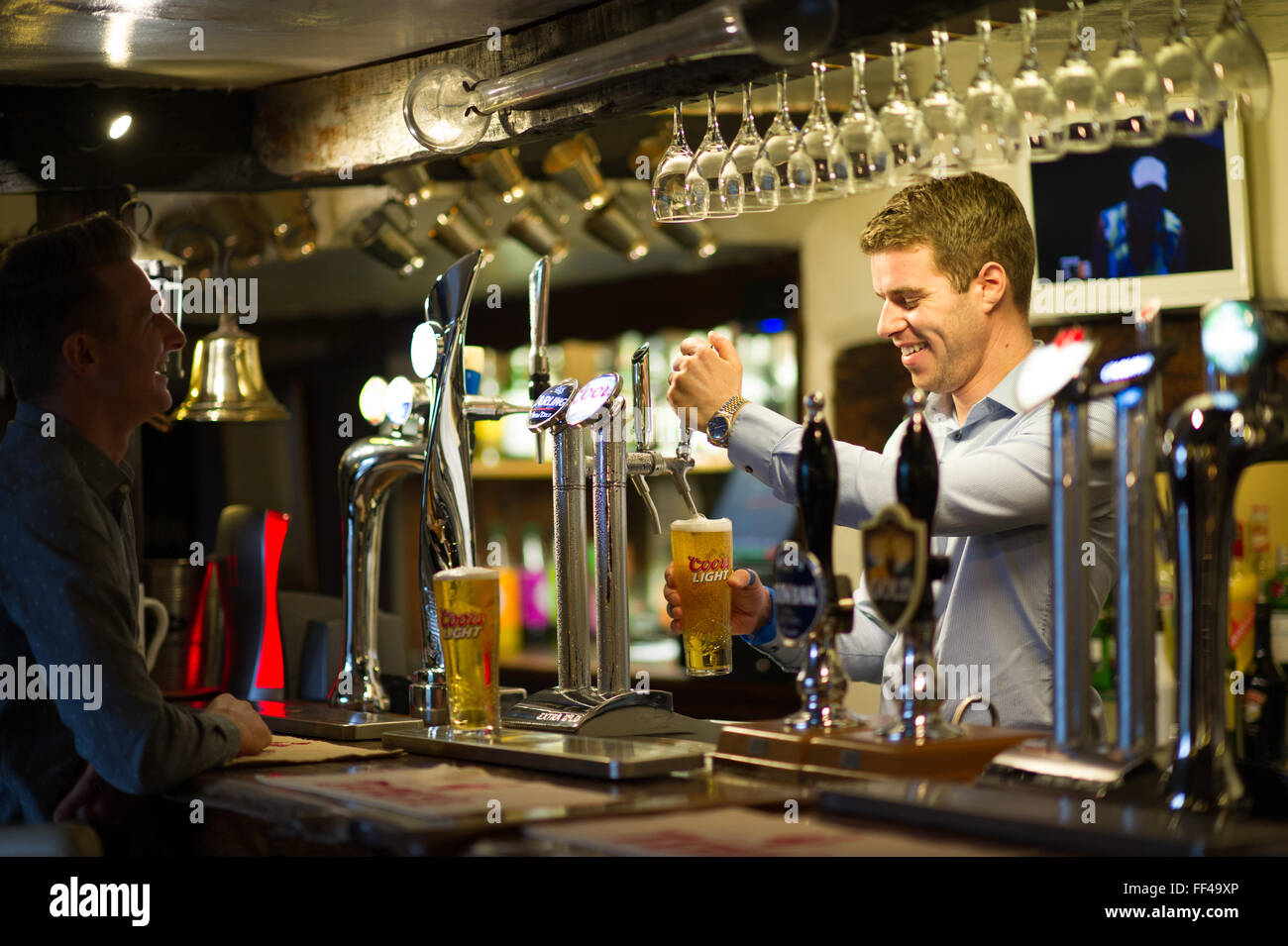 A barman pulling a pint in a traditional English pub - Stock Image