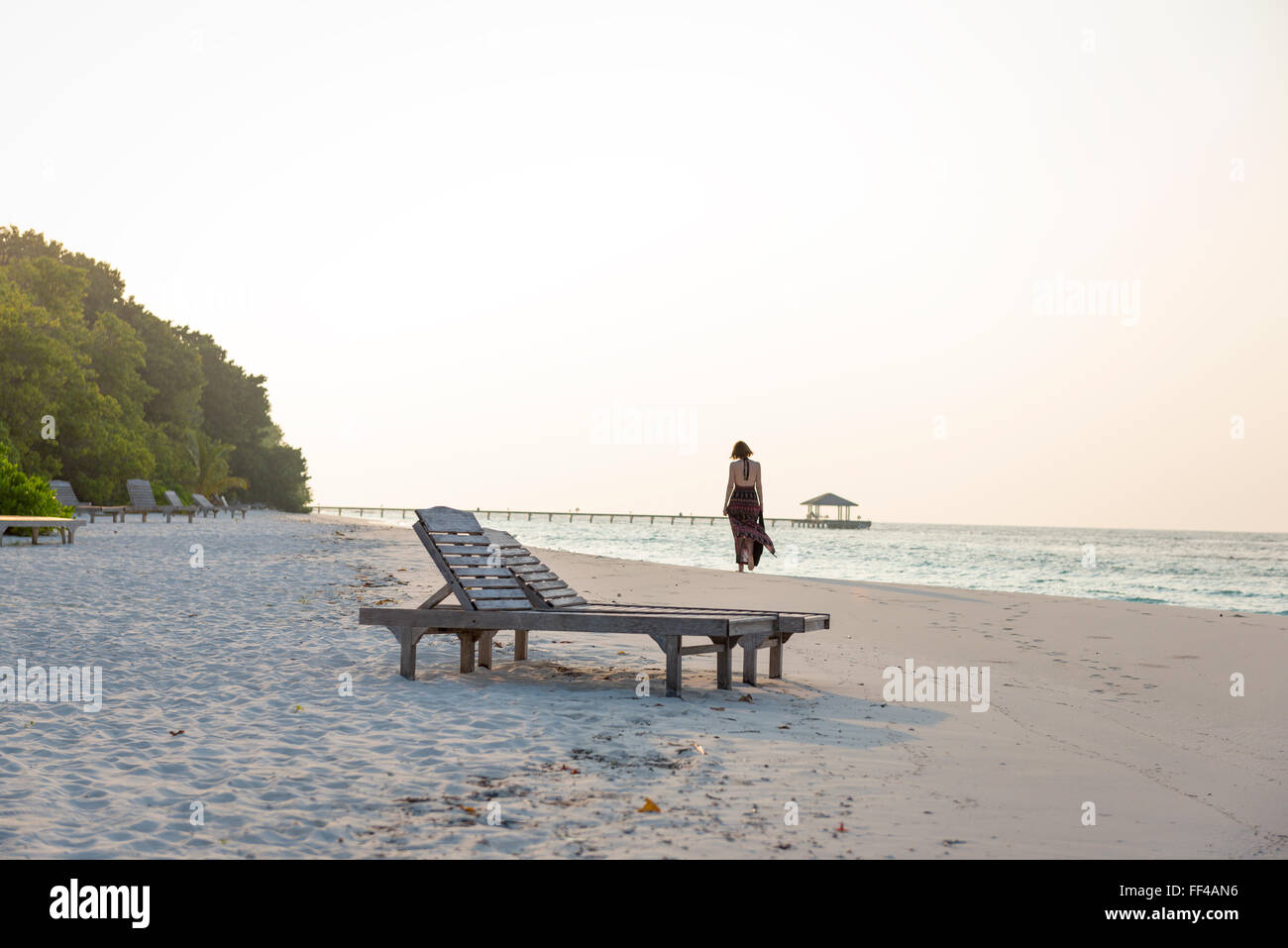 sunrise at a lonely beach with beautiful woman walking past. lonely mood in warm sunshine. - Stock Image