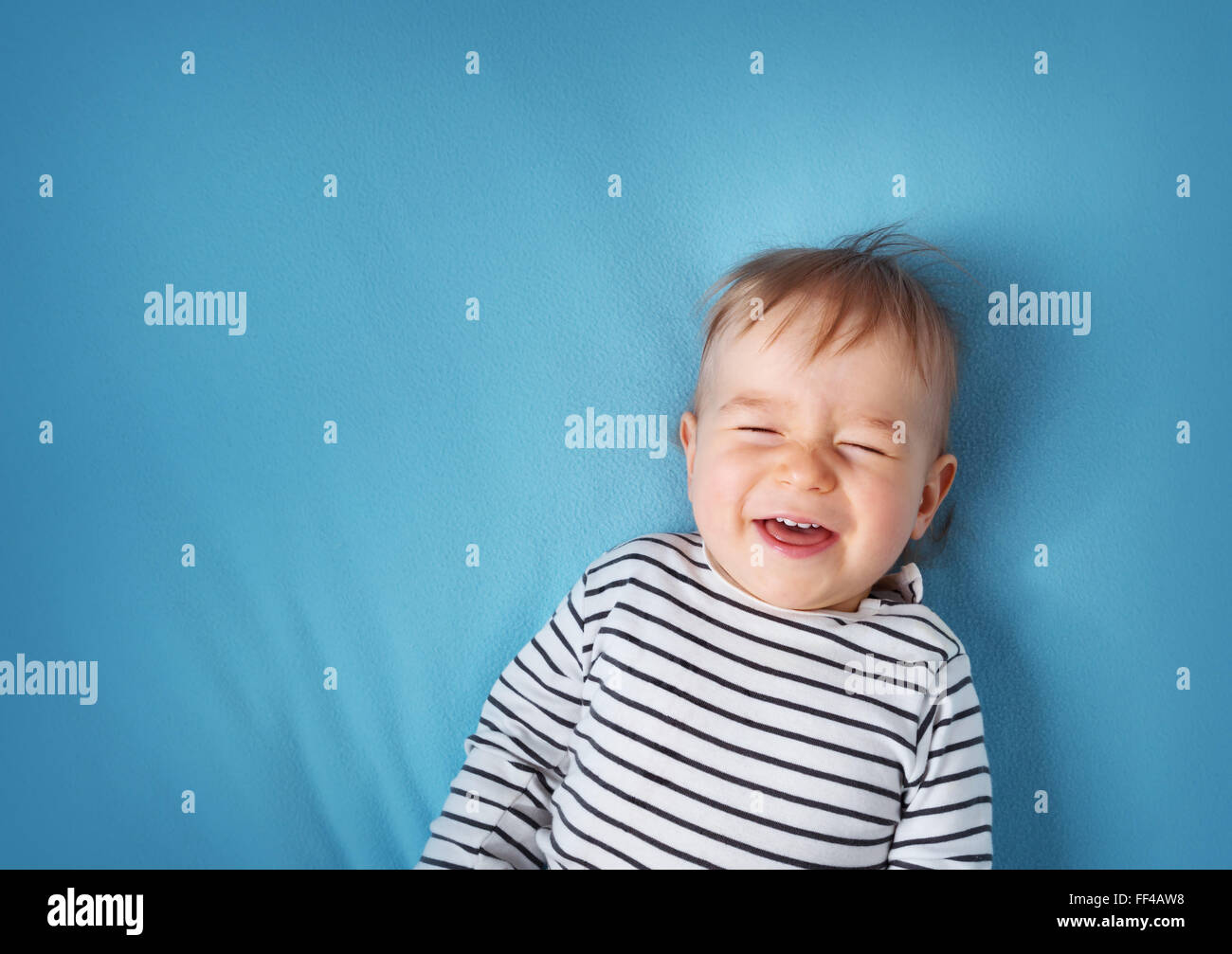little boy on blue blanket background Stock Photo