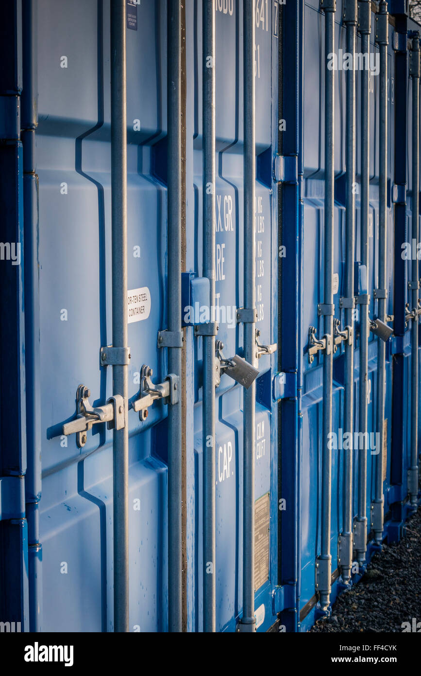 A row of Blue Self Storage Shipping Containers in a secure compound - Stock Image