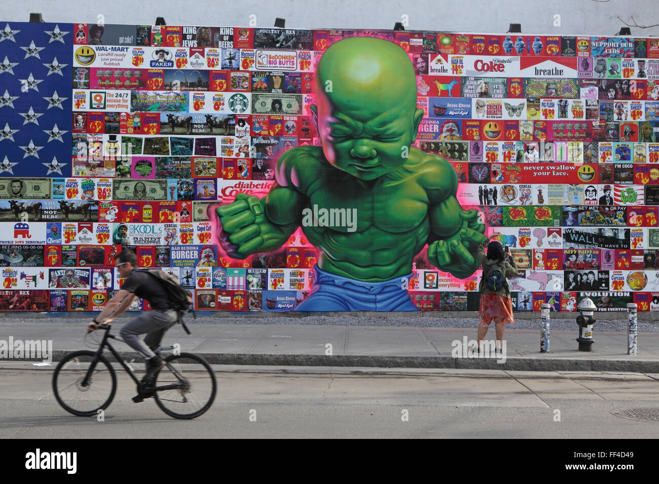 A man cycles to work past a Ron English art collage on the Bowery Mural Wall on Houston Street in New York - Stock Image
