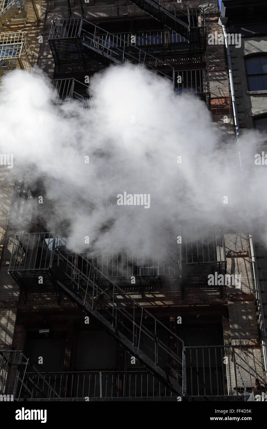 Steam like smoke drifting past a New York City building fire escape in downtown Manhattan - Stock Image